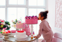 Delicious Sweet Buffet With Tiered Cake. Cute Little African American Girl Takes Candy From A Chocolate Bar.