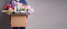 White Male Courier Holding A Large Cardboard Box With Several Bouquets