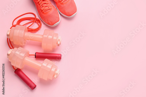 Tela Dumbbells, sport shoes and skipping rope on color background