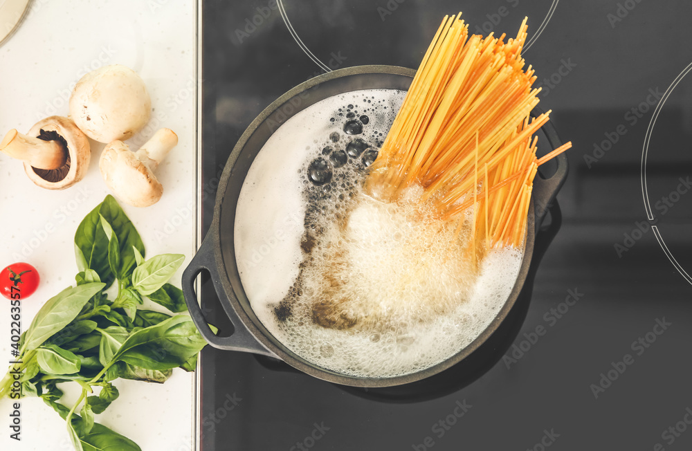 Fototapeta Pasta boiling in cooking pot on electric stove