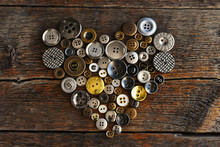 A Top View Image Of Old Vintage Buttons In A Heart Shape On An Dark Wooden Table.