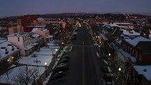 Gorgeous Aerial Establishing Shot Of Small Town In USA Covered In Snow. Trees Decorated For Christmas. Twilight In United States City.