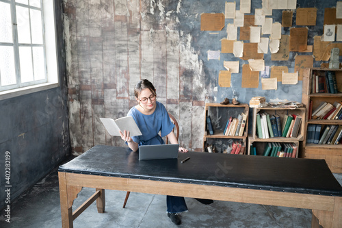 Beautiful Japanese woman with glasses working on a computer in a large, stylish room, with copy space to the right 3