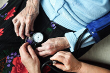 A Doctor Measures The Blood Pressure Of A 90 Year Old Female Patient. Medicine And Health Concept.