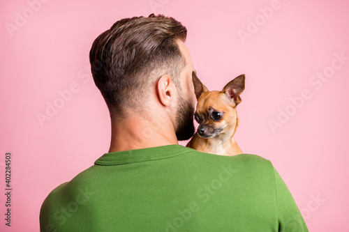 Leinwand Poster Close-up rear back behind view portrait of guy cuddling small little doggy isola