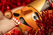 Wooden Figure In The Form Of A Soldier For Chopping Nuts Surrounded By Colored Tinsel And Hazelnuts In Bulk. New Year And Christmas. Close-up, Selective Focus.