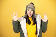 Young Beautiful Woman Wearing A Hat And A Green Winter Coat Over Yellow Background Showing And Pointing Up With Fingers Number Ten While Smiling Confident And Happy