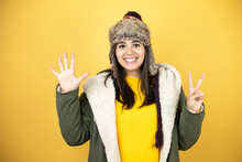 Young Beautiful Woman Wearing A Hat And A Green Winter Coat Over Yellow Background Showing And Pointing Up With Fingers Number Seven While Smiling Confident And Happy