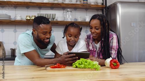 Fotografie, Obraz Happy black family reading vegetarian recipe on tablet pc cooking together in ki