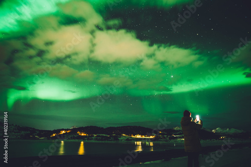 Person with phone on cold coast with aurora above