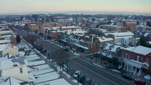 Aerial Establishing Shot Of Main Street, Small Town America, Storefronts And Colonial Homes In United States Historic Town During Winter Snow.
