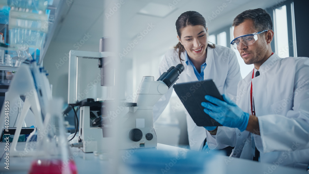 Fototapeta Modern Medical Research Laboratory: Portrait of Two Scientists Working, Using Digital Tablet, Analyzing Samples, Talking. Advanced Scientific Pharmaceutical Lab for Medicine, Biotechnology Development
