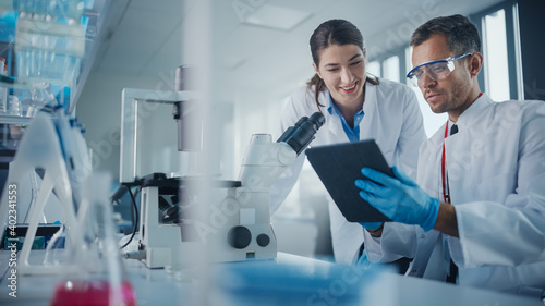 Obraz na plátne Modern Medical Research Laboratory: Portrait of Two Scientists Working, Using Digital Tablet, Analyzing Samples, Talking