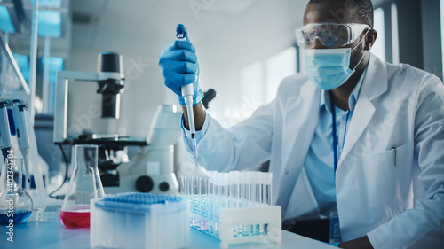 Leinwand Poster Medical Development Laboratory: Black Scientist wearing Face Mask Uses Pipette for Filling Test Tube with Liquid, Conducting Experiment