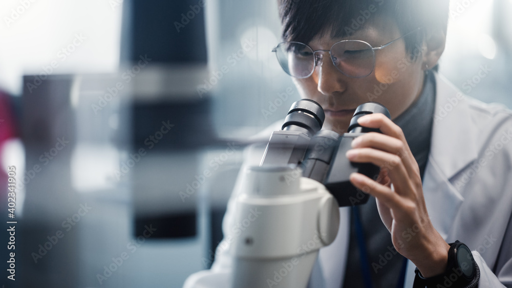 Fototapeta Medical Development Laboratory: Portrait of East Asian Scientist Looking Under Microscope, Analyzes Petri Dish Sample. Pharmaceutical Lab doing Medicine, Biotechnology, Microbiology, Drugs Research.