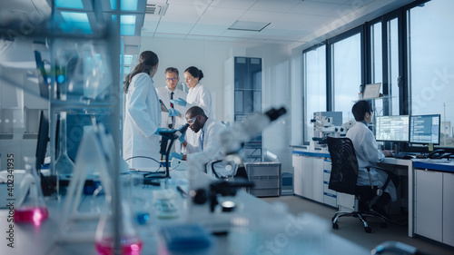 Photo Medical Science Laboratory with Diverse Multi-Ethnic Team of Microbiology Scientists Have Meeting on Developing Drugs, Medicine, Doing Biotechnology Research