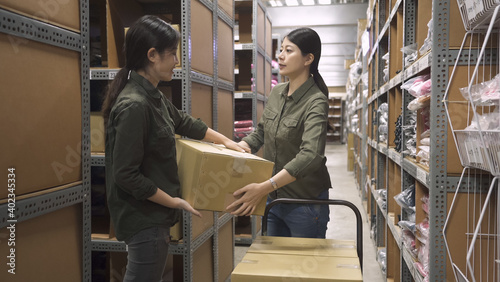 Fotografía two warehouse asian chinese female worker colleague passing cardboard box in large depot of factory