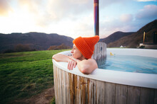 Happy Romantic Woman In Big Beanie Hat Sit Inside Warm Big Wooden Hot Tub. Weekend Getaway At Hipster Glamping With Wood Burner. Heated Tub In Autumn Cold Weather
