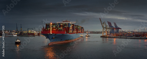 Large container ship at a terminal in the early evening