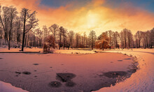 Sunset Over Park With Small Lake And Covered In Snow Trees