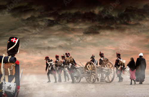 Fototapeta French grenadier watching napoleonic soldiers and women marching and pulling a cannon in plain land, countryside with stormy clouds