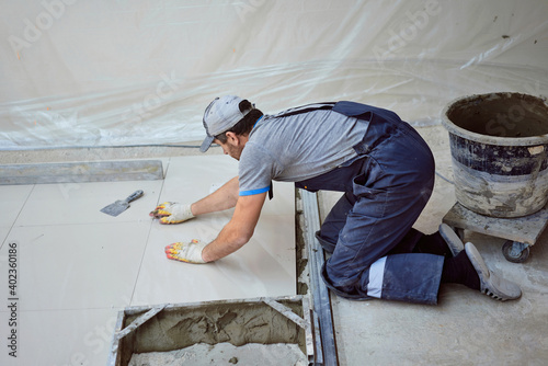 man lays stoneware on a construction site Fotobehang