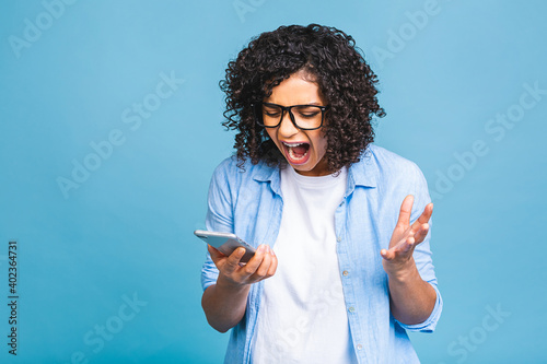 Fotografering Attractive curly american female with Afro hairstyle looks agitated at screen of smart phone, impressed by message content recieved from friend, has shocked surprised facial expression