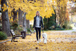 canvas print picture - Aattractive young woman walking with her lovely golden retriever dog in the park in autumn.