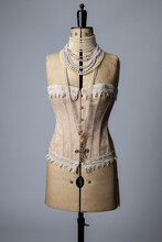 A Vintage Dressmakers Dummy Wearing A Corset And Pearl Necklaces