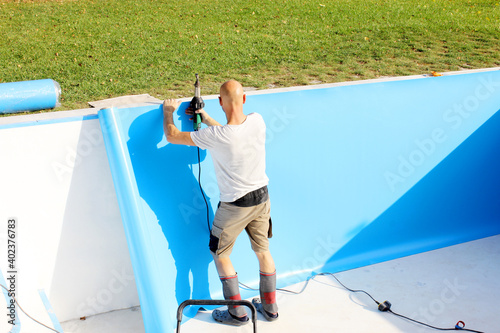 Canvas Print A worker welds plastic cover for water pool
