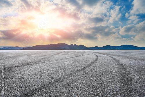 Fototapeta Asphalt road ground and mountain at sunset.Race track road and mountain background. obraz