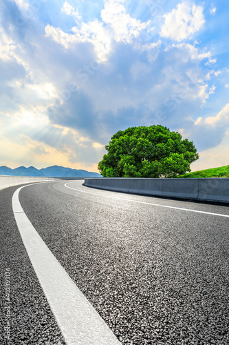 Asphalt road and mountain at sunset.Road and mountain background.