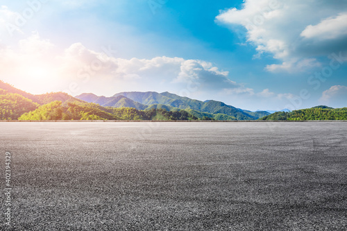 Obraz Asphalt road ground and mountain at sunset.Race track road and mountain background. - fototapety do salonu