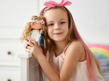 Happy Kid Girl In Home Clothing And Headband With Bow Plays Takes Picture Is Posing With Her Favorite Doll At Home. Happy Childhood, Cheerful Lifestyle, Games, Comfortable Pastime, Hobby Concept