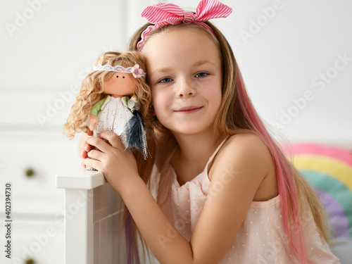 Valokuvatapetti Happy kid girl in home clothing and headband with bow plays takes picture is posing with her favorite doll at home