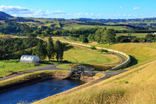 A Water Pipeline Emerges From A Reservoir And Snakes Across The Countryside. Part Of A Hydroelectric Power Scheme At Ruahihi, New Zealand