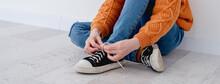 Little Girl Tying Shoelace On Sneakers