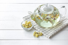 Teapot With Floral Tea And Dry Flowers On Light Background