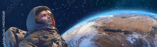 Fototapeta A female astrounaut in outer space against the Earth planet on background obraz