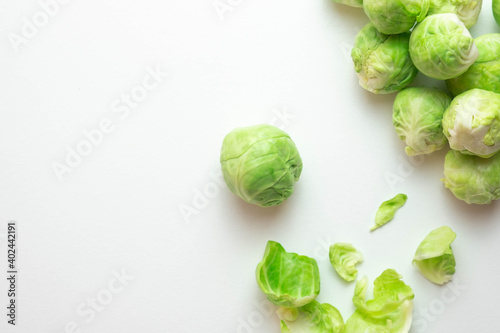 Fototapeta ripe Brussels sprouts lie on the table, next to its leaves obraz