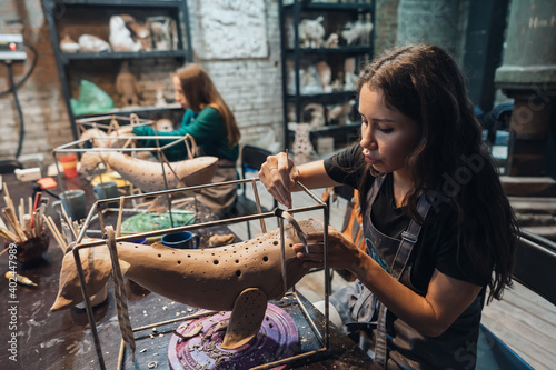 Obraz Portrait of young woman enjoying favorite job in workshop. - fototapety do salonu