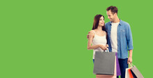 Love, Holiday Sales, Shop, Retail, Consumer Concept - Couple With Shopping Bags, Looking At Each Other. Green Color Background. Copy Space For Text.