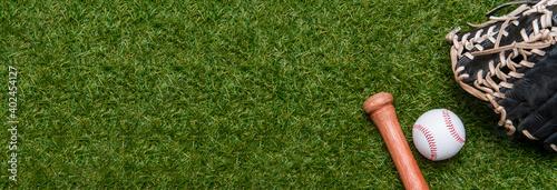 Fotografering Baseball bat, glove and ball on green grass field