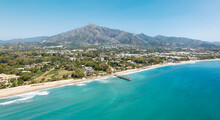 Unique Aerial View Of Luxury And Exclusive Area In Marbella, Golden Mile Beach, View Of Puente Romano Bridge And In Background Famous La Concha Mountain. Emerald Water Colour