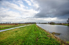 Dramatic Skies Over A Dutch Polder Landscape, With The Canal Surrounding Zuidplaspolder Near Gouda With A Higher Water Level Than The Adjacent Oostpolder