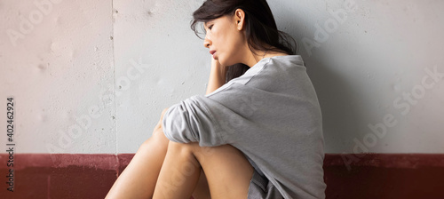 Fototapeta Unhappy woman sits and hugs her knees up to the chest,with upset and sad feeling