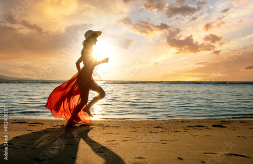 Obraz Young woman wearing long red dress and straw hat running on sand beach at sea shore enjoying view of rising sun in early summer morning. - fototapety do salonu