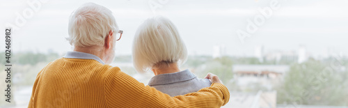 Canvas Print back view of elderly husband hugging wife on terrace on blurred background, bann