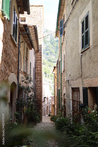 Fototapety, obrazy: Small cobblestone road in old Spanish mountain village Valldemossa with green hills in background, Mallorca, Spain