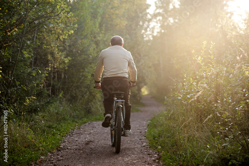 Old caucasian man riding a bike outdoor Fotobehang